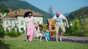 无忧无虑的年轻白种人家庭沿握手,家庭的愉快的面孔的绿草愉快地跑 股票录像