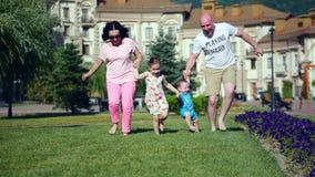 无忧无虑的年轻白种人家庭沿握手,家庭的愉快的面孔的绿草愉快地跑 影视素材