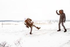 无忧无虑的愉快的年轻夫妇获得乐趣一起在冬天森林地投掷的雪球的雪在彼此在一次假装战斗期间 免版税库存图片