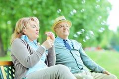 无忧无虑的成熟夫妇吹的泡影在公园 库存照片