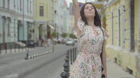 无忧无虑的有购物带来的年轻女人佩带的夏天礼服在设法的手上乘坐在街道的出租汽车老 股票录像