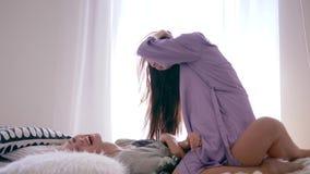 无忧无虑的生活方式,愉快的女孩在女朋友跳跃在睡衣派对期间,并且他们在慢动作的床上落 股票视频