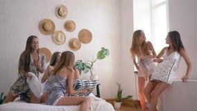 无忧无虑的生活方式,许多女孩享受与枕头的比赛在卧室在大会串 股票视频
