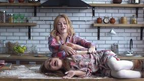 无忧无虑的美丽的年轻在面粉沉重弄脏的母亲和女儿唬弄在厨房里 妈妈和孩子获得乐趣 股票视频