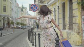 无忧无虑的美丽的有购物带来的年轻女人佩带的夏天礼服在设法的手上乘坐在街道的出租汽车 股票视频