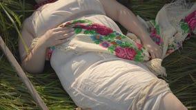 无忧无虑的超重妇女画象有一个花圈的在她的说谎在夏天领域的草的头在大镰刀附近 股票录像