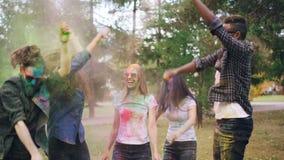 无忧无虑的青年人获得乐趣在跳,笑和投掷五颜六色的粉末油漆的Holi节日户外  股票视频