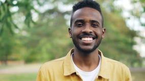 无忧无虑的非裔美国人的人慢动作画象站立在公园单独微笑和看的时髦衣物的 影视素材