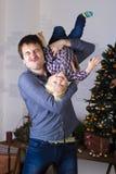 无所事事在与礼物的圣诞树的父亲和儿子 免版税库存图片