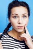 无所事事在蓝色背景关闭的年轻俏丽的妇女微笑 免版税库存照片