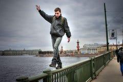 无所畏惧的人在桥梁栏杆做极值的步行  库存图片