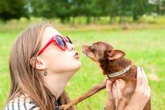 无条件的爱 亲吻她的棕色玩具狗d的十几岁的女孩 库存照片