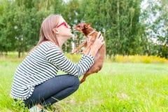 无条件的爱 亲吻她的棕色玩具狗d的十几岁的女孩 图库摄影
