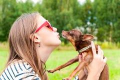 无条件的爱 亲吻她的棕色玩具狗d的十几岁的女孩 免版税库存图片