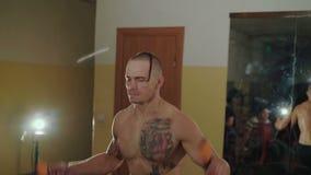 无毛与纹身花刺释放与绳索的战斗机跃迁在健身房 4K 股票录像