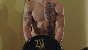 无毛与纹身花刺释放战斗机推力在健身房的坚硬杠铃 迟缓地 股票录像