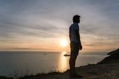 无法认出的人敬佩在一座山的日落与海景 侧视图 免版税库存照片
