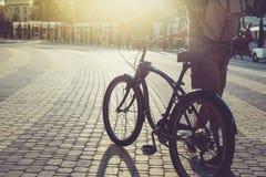 无法认出的人走与在夏天正方形的一辆自行车在早晨每日定期生活方式 库存图片