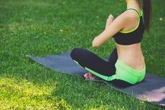 无法认出的坐在padmasana的女子实践的瑜伽 免版税库存照片