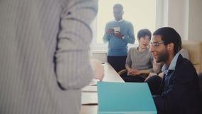 无法认出的女性上司激发工作者在不同种族的办公室队会议上 在现代工作场所4K的不同的小组 股票视频