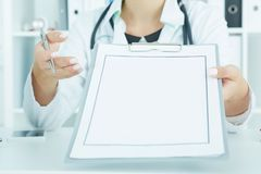 无法认出的女性医生递拿着有空白的纸片的剪贴板 免版税库存照片