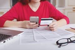 无法认出的女性模型播种的射击在红色毛线衣的坐在工作表上围拢与纸和便携式计算机,用途 免版税库存图片