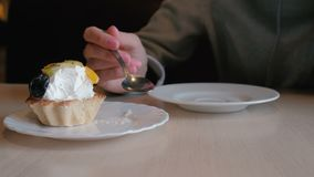无法认出的妇女吃与匙子的一个蛋糕 关闭 影视素材