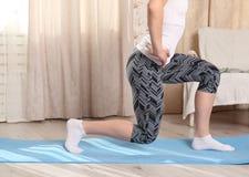 无法认出的妇女在客厅在家做健身锻炼在一张蓝色席子,做蹲坐 腿和身体 免版税图库摄影