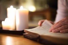 无法认出的妇女读书圣经 在她旁边的灼烧的蜡烛 图库摄影