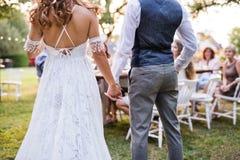 无法认出的新娘和新郎与客人结婚宴会的外面在后院 库存照片