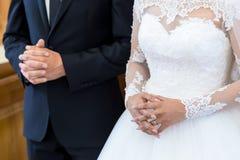无法认出的新娘和新郎在基督徒婚礼期间的教会里 新娘的手在关闭  免版税图库摄影