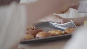 无法认出的母亲在桌上把新鲜的被烘烤的饼放,她饥饿的儿子采取面包店 有大友好的noizy的家庭 影视素材
