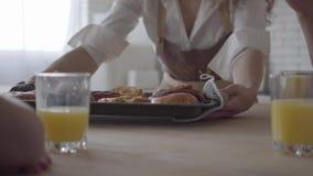 无法认出的母亲的手在桌上把新鲜的被烘烤的饼放,她饥饿的儿子采取面包店 大友好noizy 股票录像