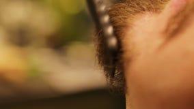 无法认出的理发师裁减使用飞剪机和刷子的刮胡须他的男性客户 影视素材
