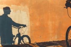 无法认出的男性骑自行车者的阴影一种五颜六色的墙壁每日定期生活方式的 库存图片