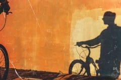 无法认出的男性骑自行车者的阴影一种五颜六色的墙壁每日定期生活方式的 免版税库存图片