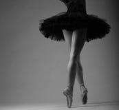 无法认出的芭蕾舞女演员在演播室,黑芭蕾舞短裙成套装备 长的腿,黑白图象 免版税库存图片