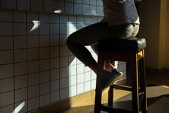 无法认出的行家女孩坐在一个固定的咖啡馆后,餐馆酒吧的酒吧的一把椅子 免版税图库摄影