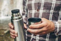 无法认出的远足者人倒茶或咖啡从休息的热水瓶远足概念 免版税库存照片