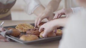 无法认出的饥饿的儿子采取面包店 食用大友好的noizy的家庭与甜点和橙汁过去的早餐一起 股票录像