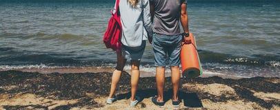 无法认出的年轻夫妇旅客站立在海滨和享受看法冒险旅行旅途的男人和妇女放松概念 免版税库存图片
