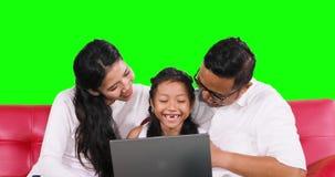 无牙的女孩和父母使用在沙发的膝上型计算机 影视素材