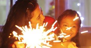 无牙的演奏灼烧的闪烁发光物的女孩和母亲 股票录像