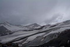 无生命的岩石积雪的山,从Elbrus,北高加索,俄罗斯倾斜的看法  免版税图库摄影