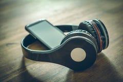 无线听与倾斜反对黑顶上的耳机的一个黑手机的音乐概念在木表 免版税库存照片