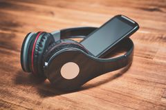 无线听与倾斜反对黑顶上的耳机的一个黑智能手机的音乐概念在木表 免版税库存图片