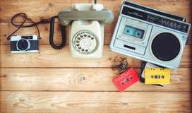 无线电盒式带录音机减速火箭的技术有减速火箭的磁带、葡萄酒电话和影片照相机的在木桌上 库存照片