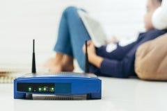 无线路由器和孩子使用一种片剂在家 路由器无线 免版税库存图片