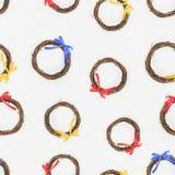 无缝的墙纸样式,从与五颜六色的丝带的分支编织的花圈 免版税库存照片