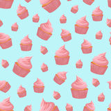 无缝的样式用在蓝色背景的桃红色杯形蛋糕 免版税库存图片